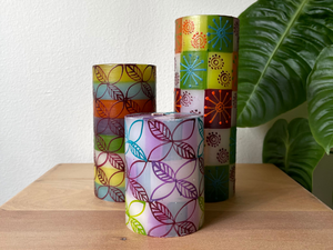 3 pillars in a variety of sizes. White base with green, orange, turquoise, and lavendar stripes. Overlay of pigment colors with a variety floral and leaf designs.