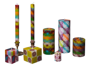 Set of 7 candles; taper pair, cubes, pillars, votive. White base with green, orange, turquoise, and lavendar stripes. Overlay of pigment colors with a variety floral and leaf designs.