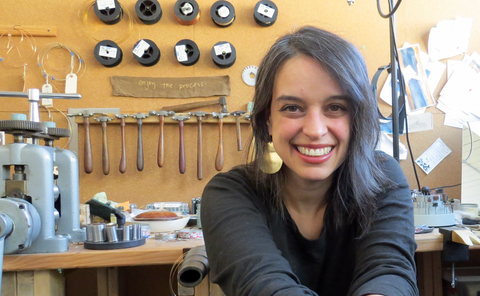 "A photo of Deb Gregoire in her studio. She is wearing large gold earrings and is smiling at the camera. In the background is her workbench, with a row of hammers and a note that says ""enjoy the process."""