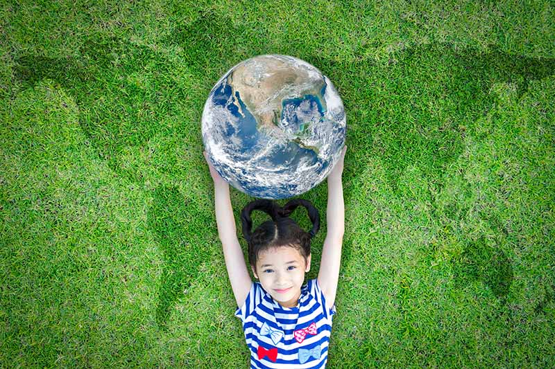 girl hold globe with continents in grass behind her
