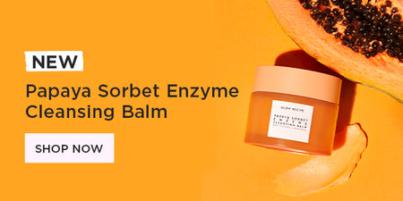 Papaya Cleansing Balm on orange background next to papaya fruit