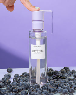 blueberry bounce gentle cleanser being dispensed and surrounded by real blueberries