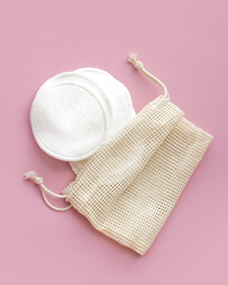 7-pack reusable cotton pads next to reusable mesh bag on pink backdrop