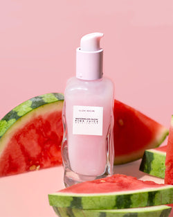 pink juice moisturizer surrounded by real watermelons against pink backdrop