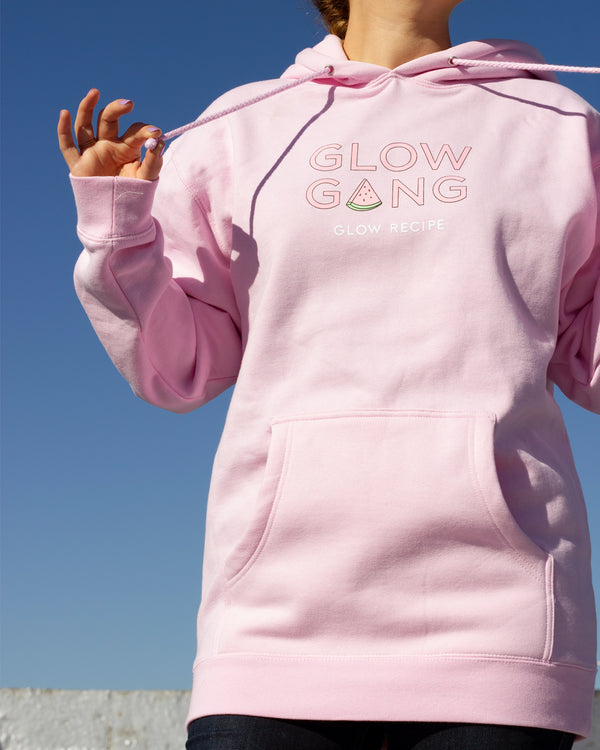 front shot of model wearing glow gang hoodie outside and pulling on hoodie strings