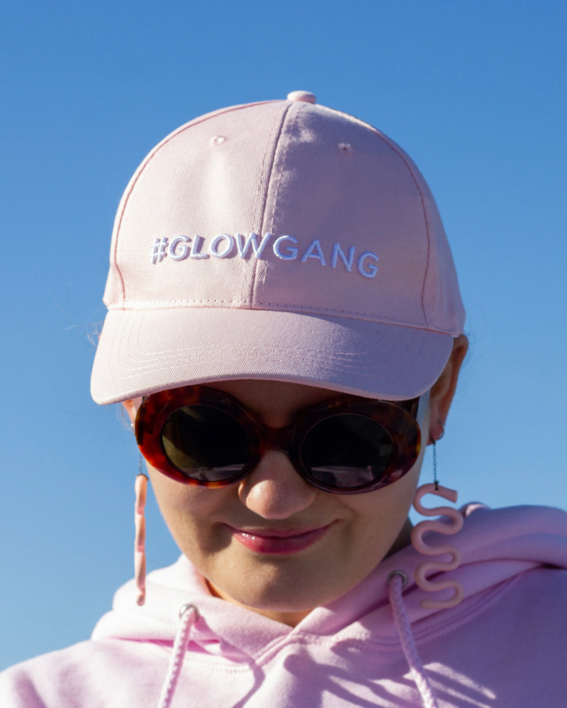 face shot of model wearing glow gang baseball cap with pink hoodie and earrings outside
