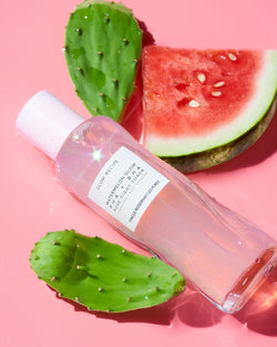 Watermelon glow PHA + BHA pore-tight toner on pink backdrop with fruit