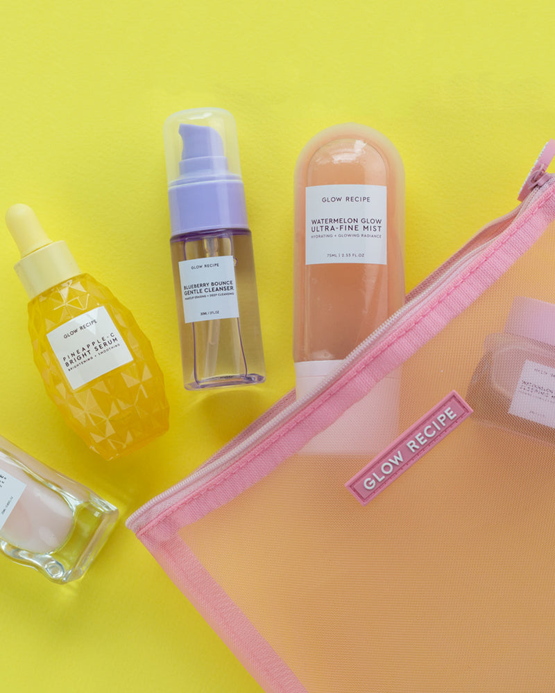 glow recipe products spilling out of pink mesh zip on yellow backdrop