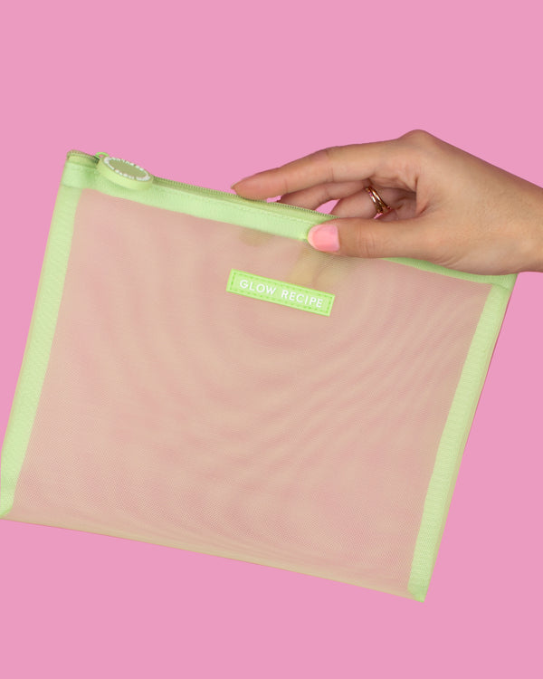 model's hand holding green mesh zip against pink backdrop
