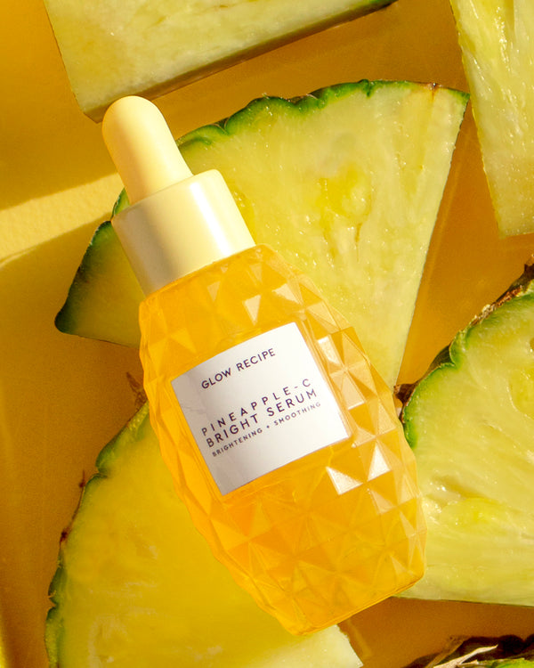 pineapple-C bright serum sitting on real pineapple fruit