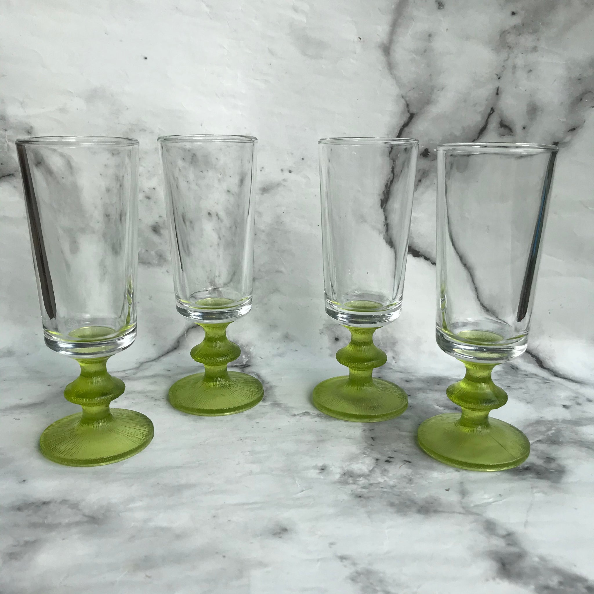 Four sherry glasses with green bulbous textured stems and clear slender bowls