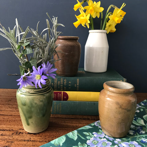A set of four old English glazed stoneware cream, green and brown jars