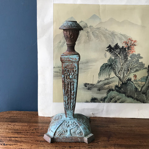 Heavy metal candlestick with plant decoration and verdigris finish