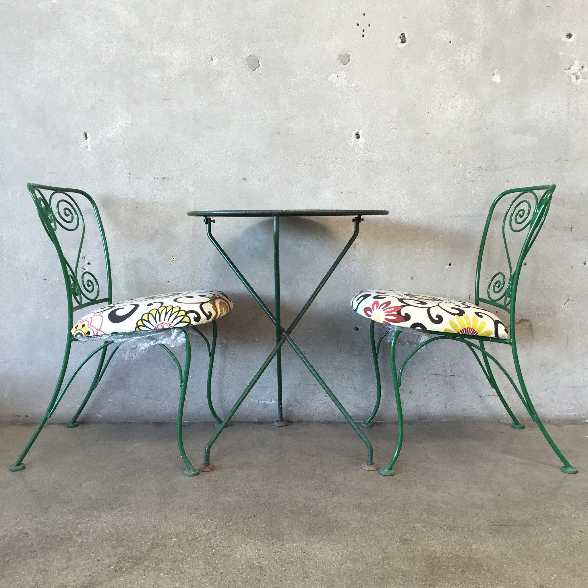 french bistro table with two wrought iron chairs