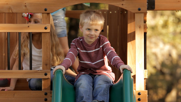 Kid on slide on wooden swingset