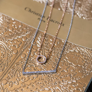 white gold vertical bar necklace and to infinity and beyond necklace on a book