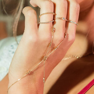 Woman wearing wanderlust hand chain and rings