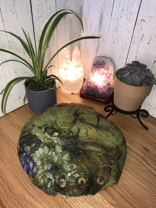 lifestyle photo of artisan round meditation floor cushion silk and merino wool with a floral pattern green with purple flowers there is a small plant a succulent and a selenite and amethyst crystal lamp