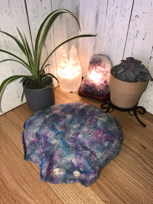 lifestyle photo of a round meditation flor cushion made of felted soft merino wool into silk fabric with silk and bamboo accents for a shimmery luster various shades of blues purple and teal with hints of pink and white small green spider plant and succulent with a selenite crystal tower lamp and amethyst crystal lamp in the background
