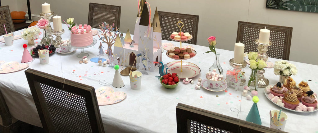 The table's set for a tea-party with a birthday cake, fairy cakes and a cardboard castle.