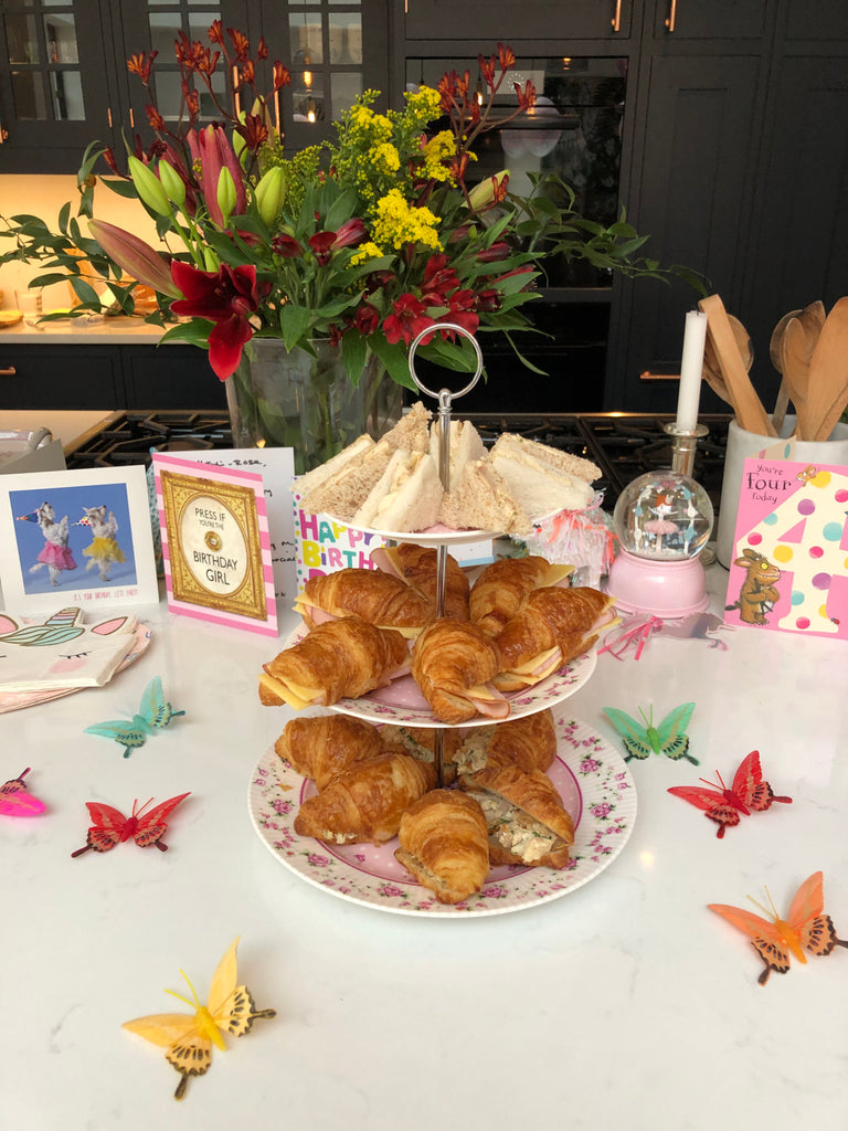 Afternoon tea-styled table with croisants and sandwiches.
