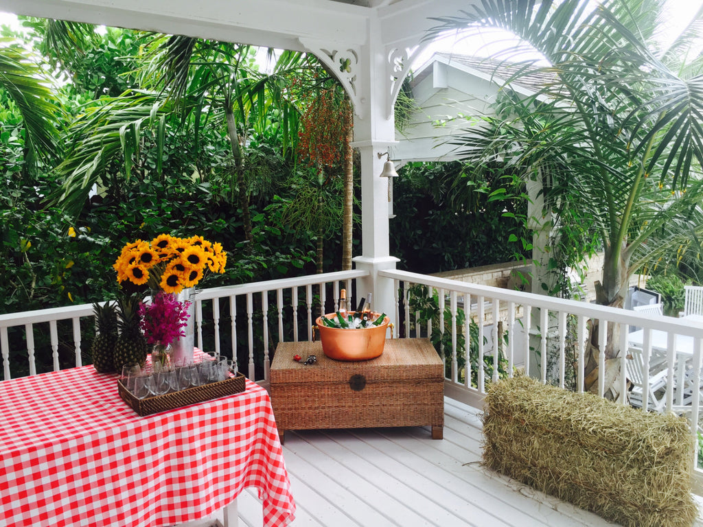 Photograph of gingham-covered tables ready for party and a bail of hay.