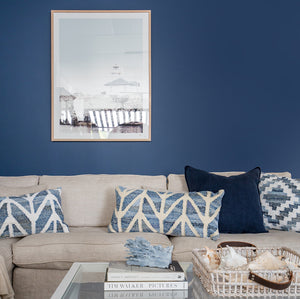 Coastal style denim blue and sustainable jute rectangle cushion in herringbone pattern on a white couch in a beach style living room.