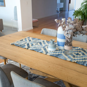 Coastal style upcycled denim blue and sustainable jute table runner in Aztec pattern on a timber table in a dining room.