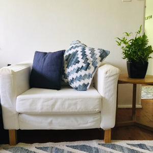 Coastal style denim blue and white square cushion in Aztec pattern styled on a armchair in living room.