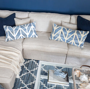 Coastal style denim blue and sustainable jute rectangle cushion in herringbone pattern on a white couch in a coastal styled living room.