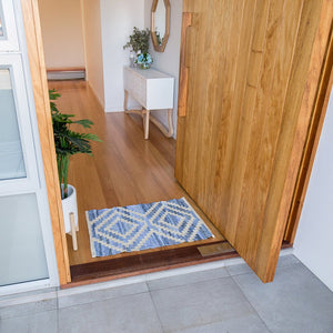 Coastal style upcycled denim blue and sustainable jute door mat in Aztec pattern in an entry way front door.
