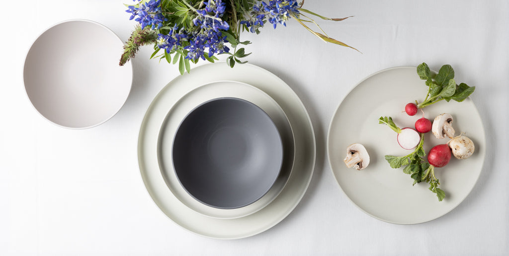 Collection of Zungleboo eco-friendly plates and bowls with veggies and flowers