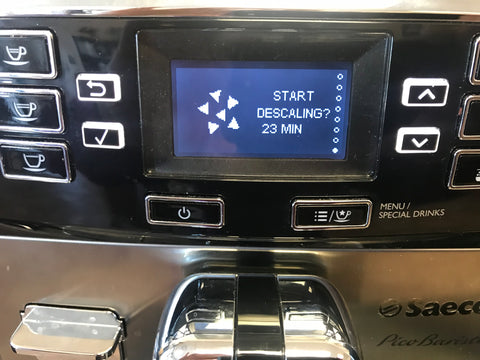 Front panel of an espresso machine indicating descaling required