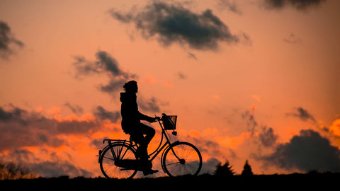 A woman riding her bike into sunset