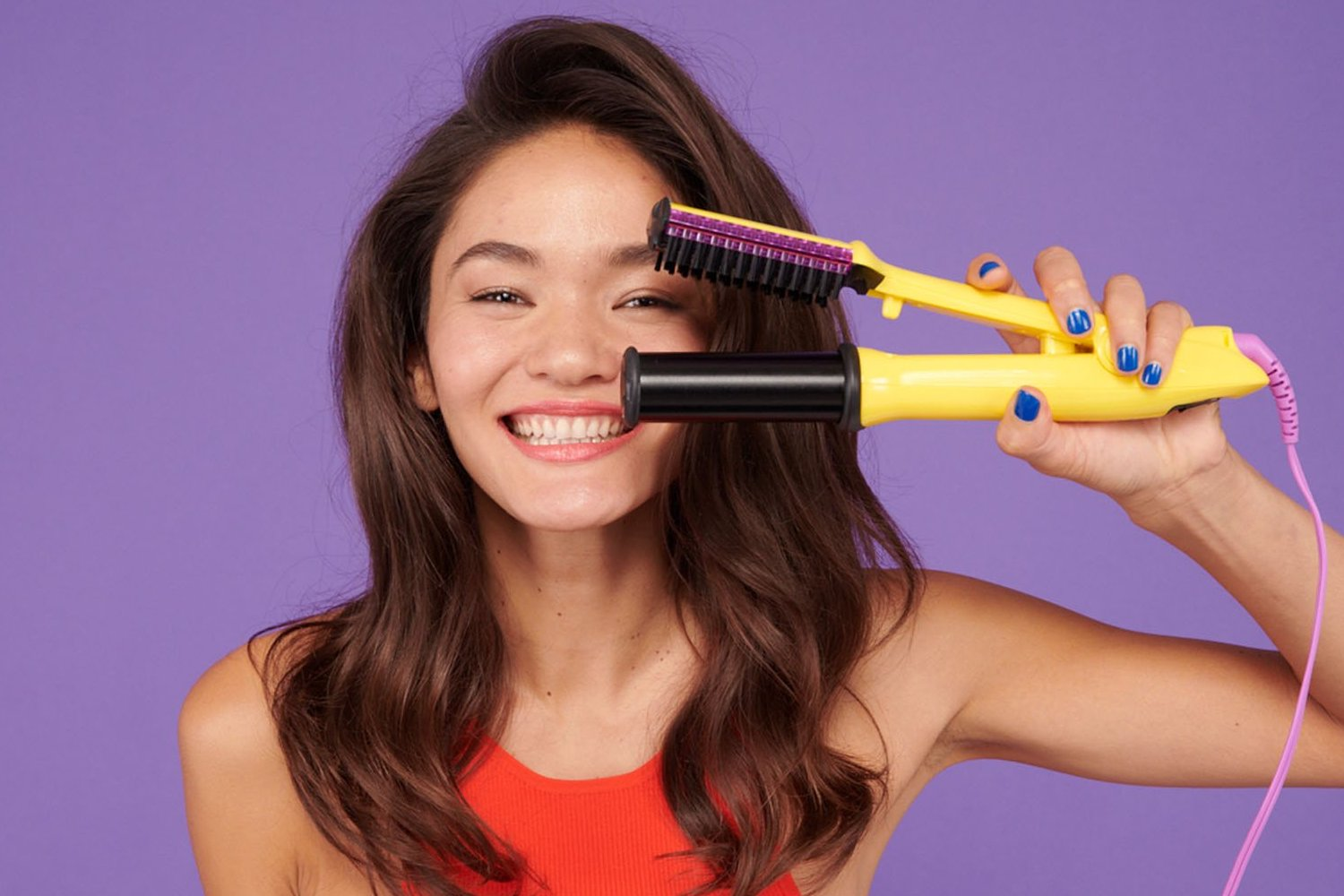 Woman smiling and holding out the Styling Iron in front of her