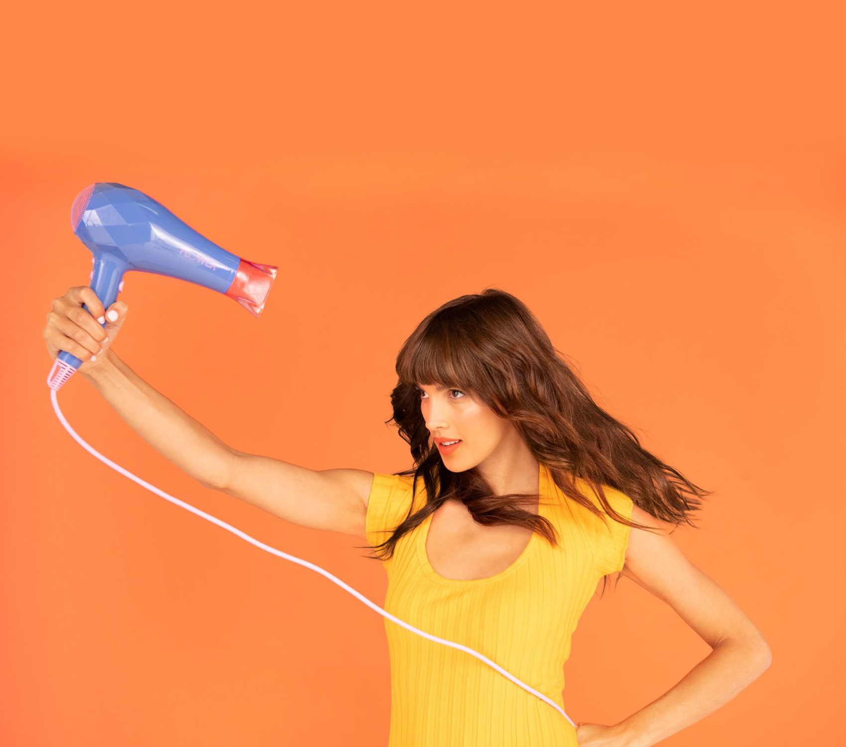 A woman holding the Ionic Pro Dryer over her head