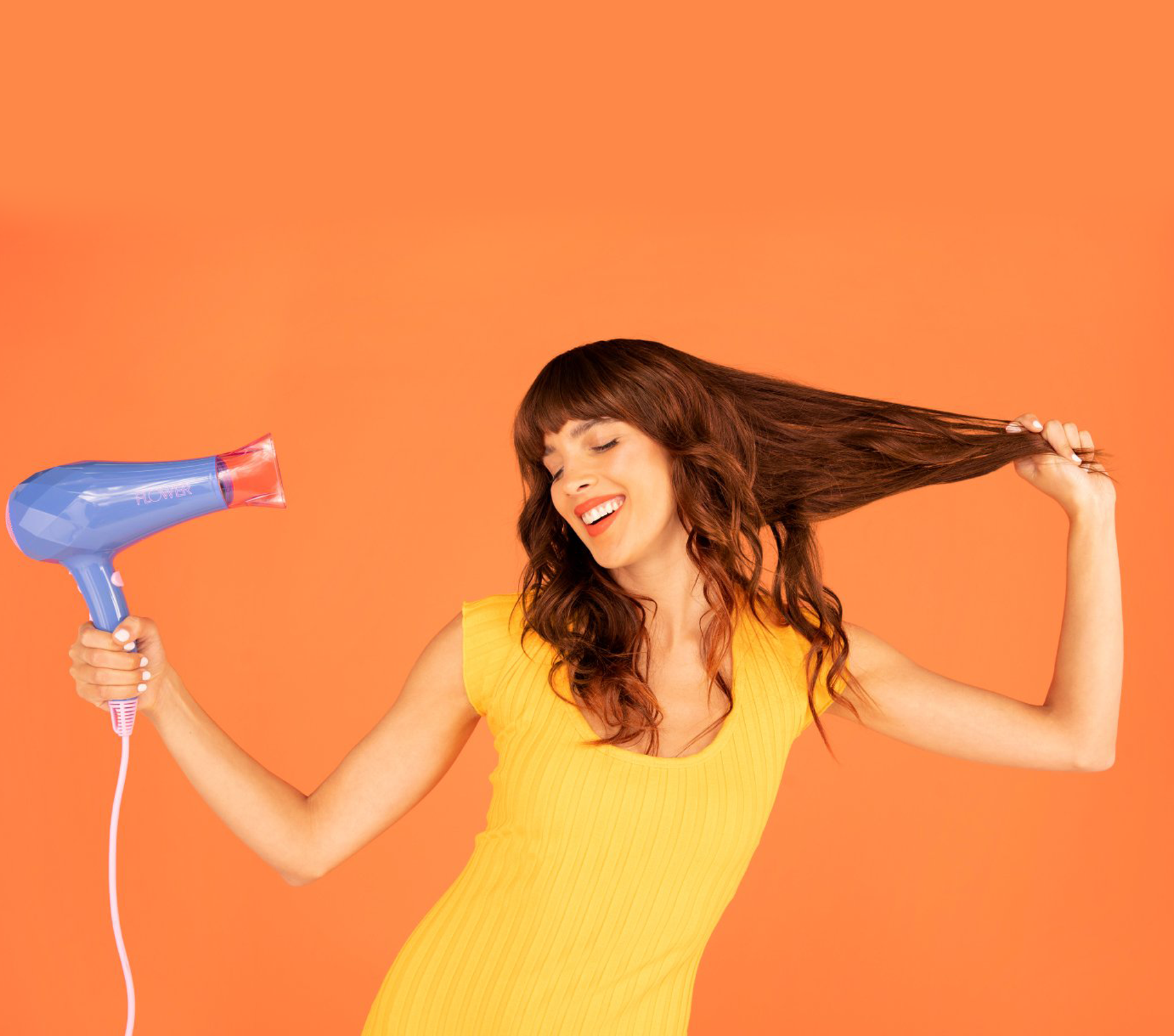 Woman blow drying her outstretched hair