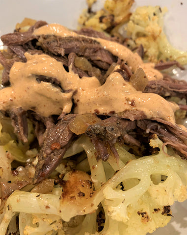 cooked beef brisket with a Mexican style barbacoa sauce, served over a bed of roasted cauliflower