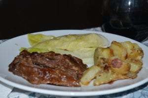 white plate with cooked beef brisket, roasted potatoes, and steamed cabbage