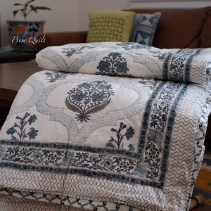 Prem quilt /rajai is a light weight traditional handblock printed quilt on soft cotton voile fabric put together by hand embroidery combining cotton padding for comfort and warmth for all seasons. This reversible quilt is a combination of traditional pattern and modern colours of deep grey and navy blue.