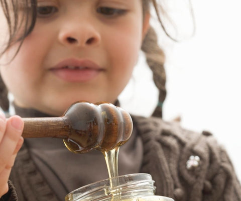 Child scooping honey from a jar.