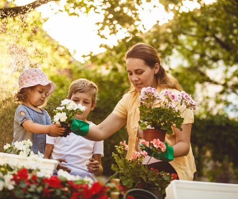 Mom planting flowers with her children