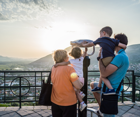 Family looking through a telescope on a family vacation.
