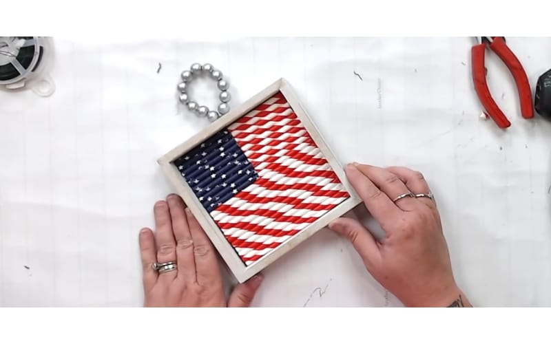 a shadowbox filled with an American flag made from paper straws