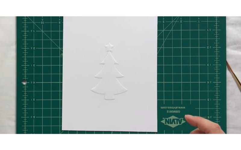 a blind embossed Christmas card on top of a craft mat