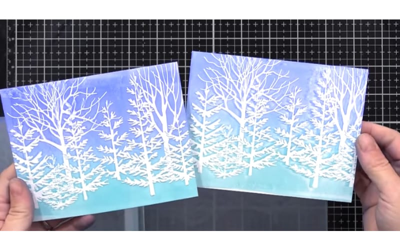 a card embossed with white trees and colorful background