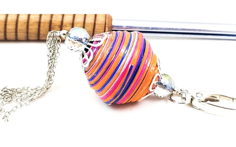 giant key fob made from paper beads with a paper bead roller in the background