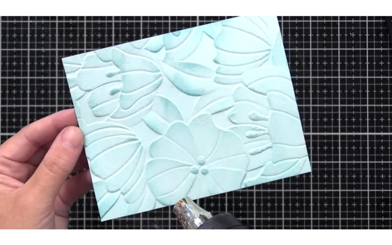 an embossed cardstock applied with heat using an embossing heat gun