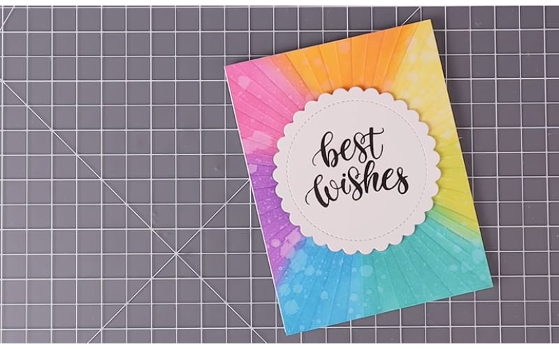 a cardstock embossed with a sunburst embossing folder and designed with multicolor distress ink