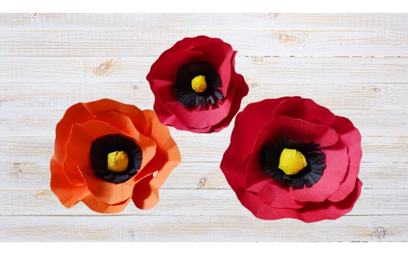 Poppy flowers made from construction paper on a distressed table